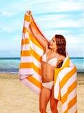 Donna con l'asciugamano alla spiaggia Immagine Stock