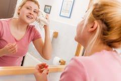 Donna con l'asciugamano bianco che pulisce fronte dopo la pulizia Fotografia Stock
