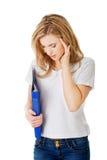 Donna con l'emicrania che tiene un raccoglitore Fotografia Stock
