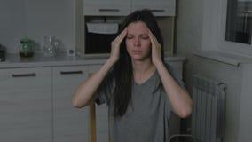 Donna con l'emicrania nella cucina alla notte Insonnia e depressione stock footage