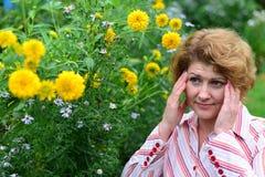donna con l'emicrania vicino ai fiori gialli Fotografia Stock Libera da Diritti