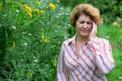 donna con l'emicrania vicino ai fiori gialli Immagini Stock Libere da Diritti