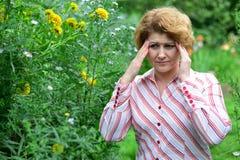 donna con l'emicrania vicino ai fiori gialli Immagini Stock