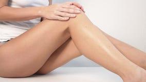 Donna con l'ente perfetto che applica la lozione di rinfresco sulle sue gambe, depilazione di concetto, skincare, cosmetici del c stock footage