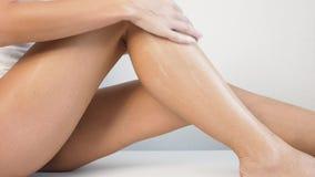 Donna con l'ente perfetto che applica la lozione di rinfresco sulle sue gambe, depilazione di concetto, skincare, cosmetici del c video d archivio