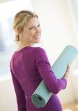 Donna con l'esercizio acciambellato Mat In Gym Fotografia Stock Libera da Diritti