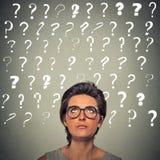 Donna con l'espressione del fronte ed i punti interrogativi imbarazzati sopra lei capa Fotografie Stock Libere da Diritti