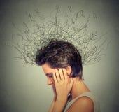 Donna con l'espressione preoccupata del fronte che prova a concentrarsi con il cervello che si fonde nelle linee Immagine Stock