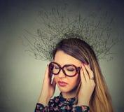 Donna con l'espressione sollecitata preoccupata del fronte e cervello che si fonde nelle linee punti interrogativi immagini stock