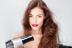 Donna con l'essiccatore lungo del colpo della holding dei capelli Fotografie Stock Libere da Diritti