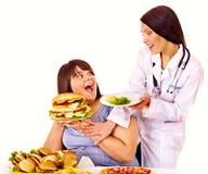 Donna con l'hamburger e medico. Immagini Stock