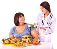 Donna con l'hamburger e medico. Fotografie Stock
