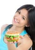 Donna con l'hamburger non sano a disposizione Immagini Stock