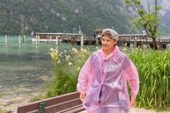Donna con l'impermeabile alla costa di Konigssee vicino a tedesco Berchtesgaden Immagini Stock