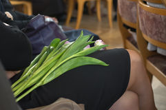 Donna con l'inginocchiamento dei fiori Immagine Stock