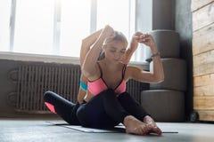Donna con l'istruttore di yoga nella classe, allungamento della curvatura della parte posteriore Immagini Stock