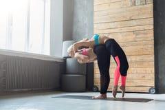 Donna con l'istruttore di yoga nella classe, allungamento della parte posteriore Immagini Stock Libere da Diritti