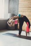 Donna con l'istruttore di yoga nella classe, allungamento della parte posteriore Fotografia Stock Libera da Diritti