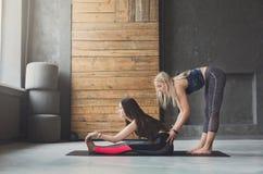 Donna con l'istruttore di yoga nella classe, posa del calzolaio di asana Fotografie Stock