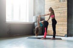 Donna con l'istruttore di yoga nella classe, posa di andata della curvatura Immagini Stock Libere da Diritti