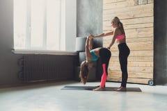 Donna con l'istruttore di yoga nella classe, posa di andata della curvatura Fotografia Stock