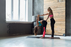 Donna con l'istruttore di yoga nella classe, posa di andata della curvatura Fotografia Stock Libera da Diritti