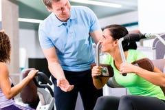 Donna con l'istruttore personale che fa forma fisica del und di sport Fotografia Stock