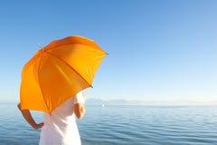 Donna con l'ombrello arancione alla priorità bassa dell'oceano Fotografia Stock