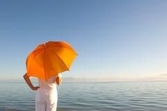 Donna con l'ombrello arancione alla priorità bassa dell'oceano Fotografia Stock Libera da Diritti