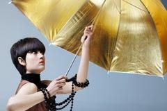 Donna con l'ombrello dell'oro. immagine stock
