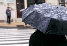 Donna con l'ombrello il giorno piovoso che aspetta per attraversare la via Fotografie Stock