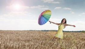 Donna con l'ombrello nel campo Immagine Stock