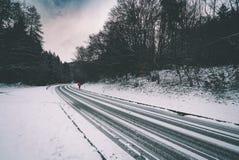 Donna con l'ombrello rosso sulla strada di inverno immagini stock