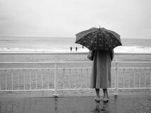 Donna con l'ombrello sulla spiaggia Fotografia Stock