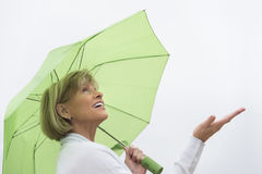 Donna con l'ombrello verde che gode della pioggia contro il chiaro cielo Immagini Stock