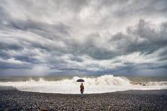 Donna con l'ombrello vicino al mare tempestoso Fotografie Stock