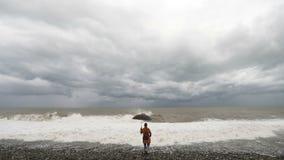 Donna con l'ombrello vicino al mare tempestoso stock footage