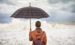 Donna con l'ombrello vicino al mare tempestoso immagini stock