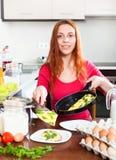 Donna con l'omelette cucinata in cucina domestica Immagini Stock Libere da Diritti