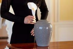 Donna con l'urna di cremazione al funerale in chiesa fotografia stock libera da diritti