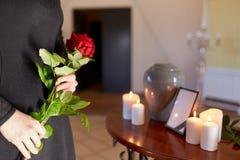 Donna con l'urna di cremazione al funerale in chiesa fotografia stock