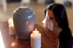 Donna con l'urna di cremazione al funerale in chiesa immagini stock