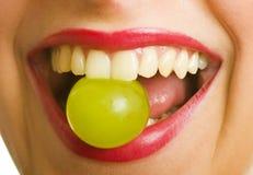 Donna con l'uva in bocca Fotografia Stock Libera da Diritti
