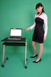 Donna con la bacchetta ed il computer portatile magici con lo schermo in bianco Immagini Stock