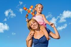 Donna con la bambina contro il cielo di estate Fotografie Stock Libere da Diritti