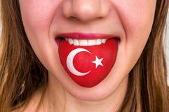 Donna con la bandiera del turco sulla lingua Immagini Stock