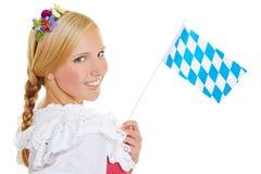 Donna con la bandiera ed il dirndl bavaresi Fotografia Stock Libera da Diritti