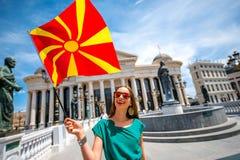 Donna con la bandiera macedone nel centro urbano di Skopje Immagini Stock Libere da Diritti