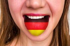 Donna con la bandiera tedesca sulla lingua Fotografie Stock