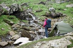 Donna con la bella vista della torrente montano in montagne di Fagaras fotografia stock